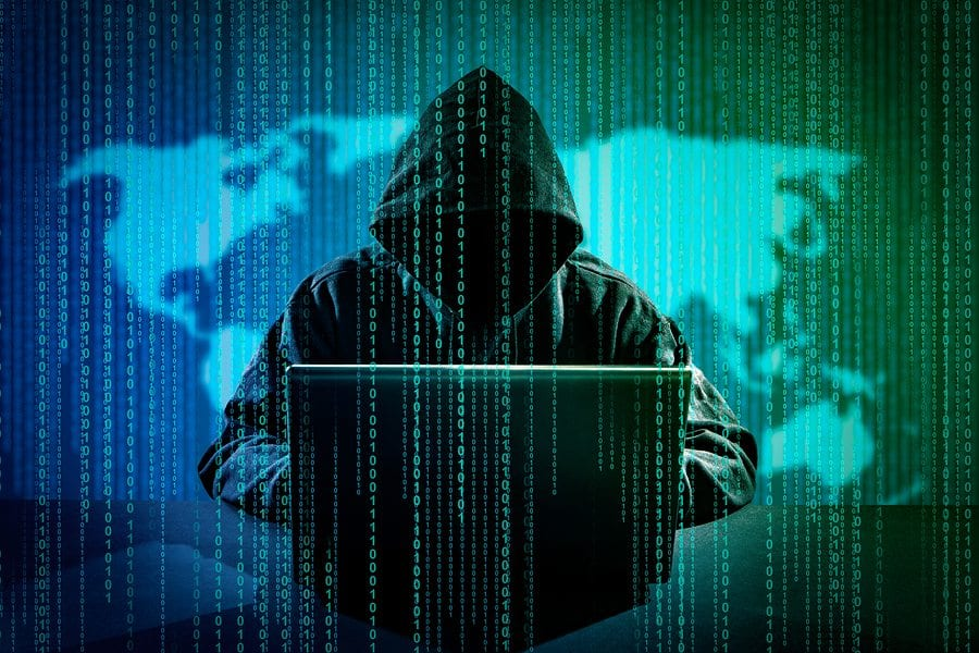 image of man in a hoodie in front of a laptop, overlaid with lines of code